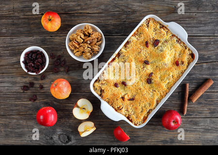 homemade apple crumble or apple crisp in baking dish - dessert consisting of baked chopped apples, topped with a crisp streusel crust, horizontal view - Stock Photo