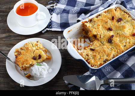 delicious apple crumble or apple crisp in baking dish and a portion on plate with homemade coconut milk ice cream. cup of tea at background, view from - Stock Photo