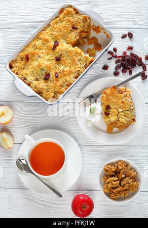 gluten free breakfast set -  apple crumble or apple crisp in baking dish and a portion on plate with coconut cream and  cup of tea on table, vertical  - Stock Photo