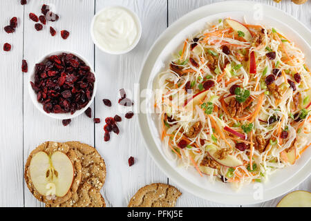 close-up of Apple Cranberry and walnuts Coleslaw salad on a white plate on wooden table with red apple slices, multigrain crispbread, yogurt sauce and - Stock Photo