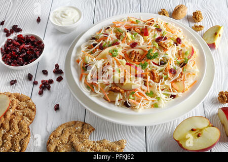 Apple Cranberry and walnuts Coleslaw salad on a white plate on wooden table with red apple slices, multigrain crispbread, yogurt sauce and nuts at bac - Stock Photo
