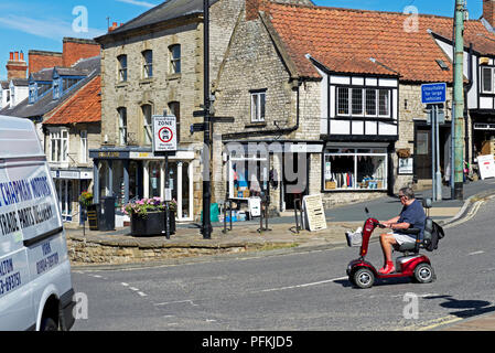 Man on mobility scooter, Pickering town,North Yorkshire, England UK - Stock Photo