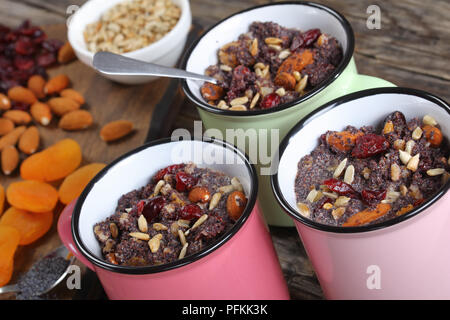 close-up of delicious christmas dessert or kutia of poppy seeds mixed with cooked whole wheat, dried fruits and nuts served in cups, view from above - Stock Photo