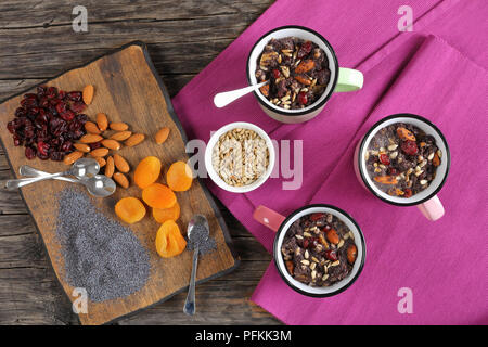 delicious christmas dessert or kutya of poppy seeds mixed with cooked whole wheat, dried fruits and nuts served in cups. ingredients on cutting board, - Stock Photo