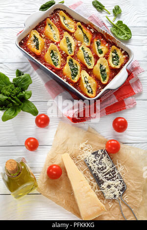 delicious big pasta shells stuffed with creamy soft cheese and spinach and baked with sauce marinara, italian recipe, vertical view from above - Stock Photo
