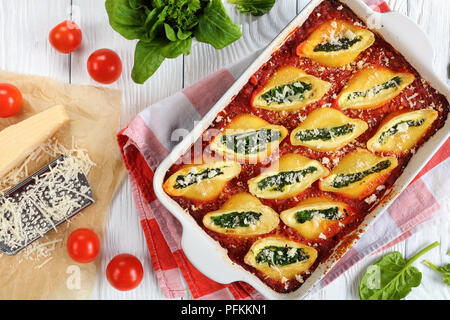 delicious big pasta baked shells stuffed with creamy soft cheese and spinach sprinkled with parmesan cheese in baking dish. grated parmesan cheese on  - Stock Photo