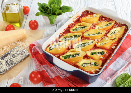 close-up of shell shape pasta stuffed with creamy soft cheese and spinach sprinkled with parmesan cheese in baking dish. grated parmesan cheese on pap - Stock Photo