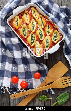 baked in oven shell shape pasta stuffed with creamy soft cheese and spinach sprinkled with parmesan cheese in baking dish with kitchen towel and woode - Stock Photo