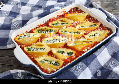 shell shape pasta stuffed with creamy soft cheese and spinach, baked in oven, sprinkled with grated parmesan cheese in baking dish with kitchen towel  - Stock Photo
