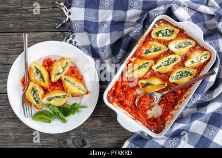 portion of shell shaped pasta stuffed with creamy soft cheese and spinach, baked in marinara sauce on dark wooden table, view from above, close-up - Stock Photo