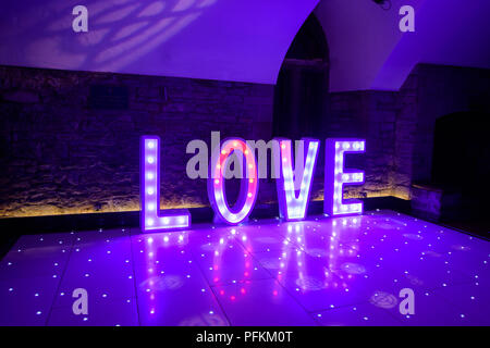 Illuminated Love sign in large letters at a wedding reception ready for the First Dance - Stock Photo