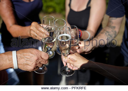 People holding glasses of champagne in a circle and bringing them together in a celebration - Stock Photo