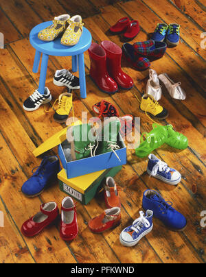 Assortment of children's shoes, two shoe boxes, and a blue stool, on a wooden floor, high angle view - Stock Photo