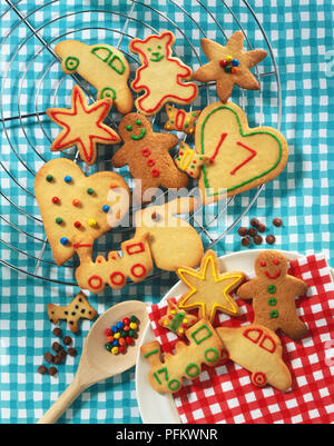 Different shaped biscuits, including hearts and stars, on a wire cooler and a plate, view from above - Stock Photo