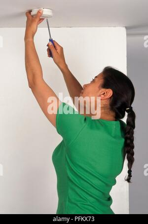 Woman screwing a smoke detector to ceiling, waist up - Stock Photo