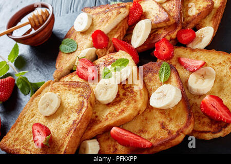buttery French toasts with appetizing, lacy brown crust and fluffy inside served on a black slate tray with fresh strawberries, banana slices, mint an - Stock Photo