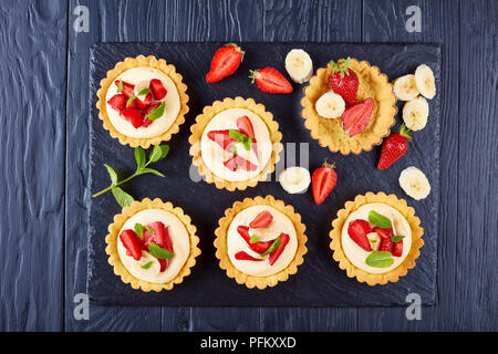 tartlets with strawberries, banana slices loaded with whipped custard cream  - diplomat on a black slate plate, view from above, close-up - Stock Photo