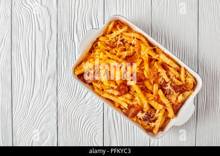 Crispy french fries smothered in melted cheese and bacon in a baking dish on a wooden table, view from above, flat lay - Stock Photo