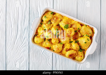 new potatoes with cheddar cheese butter sauce in a baking dish on a white wooden table, view from above, flat lay - Stock Photo