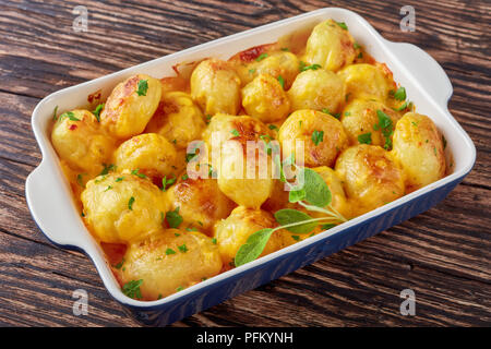 whole new potatoes baked in oven with cheddar cheese butter sauce, parsley and sage in a baking dish on a rustic wooden table, view from above, close- - Stock Photo