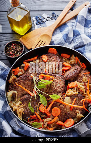chicken liver pancakes with carrot, onion, sage leaves and spices in a skillet on a black wooden table with kitchen towel and spatulas at the backgrou - Stock Photo