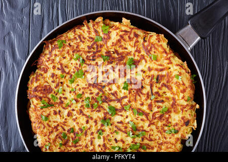 delicious swiss rosti or potato pancake sprinkled with finely chopped parsley in a pan on a black wooden table, close-up, macro - Stock Photo
