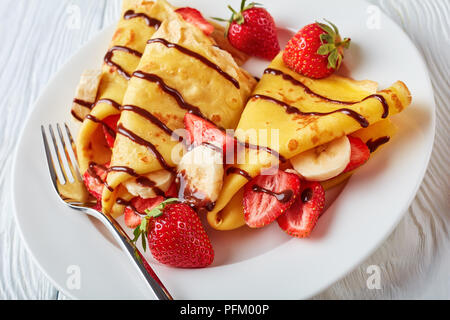 thin pancakes or crepes on a white plate with strawberries, banana slices and chocolate cream, horizontal view from above, close-up - Stock Photo