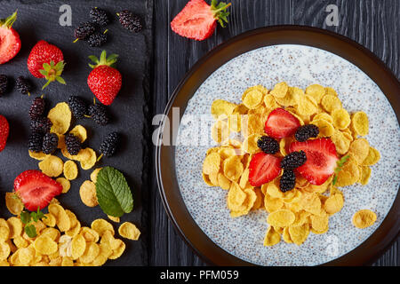 Healthy breakfast - Corn flakes with chia seeds pudding, fresh strawberry,and mulberries in a bowl on black wooden table with ingredients on cutting b - Stock Photo