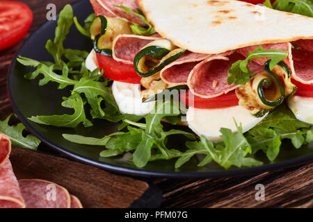 open sandwich - italian piadina with mozzarella, tomato, salami slices, grilled zucchini and arugula on a black plate with ingredients on a cutting bo - Stock Photo