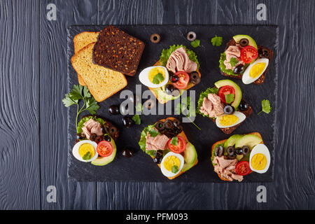 tuna open sandwiches with avocado slices, lettuce, tomatoes, black olives and hard boiled egg on a rye and corn toasted bread on a black slate tray on - Stock Photo