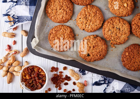 freshly baked Oatmeal Cookies with orange zest, raisins and peanuts on a baking tray with wooden spatulas and kitchen towel, view from above, flat lay - Stock Photo