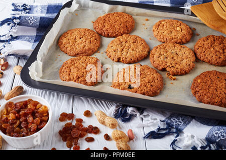 freshly baked Oatmeal Cookies with orange zest, raisins and peanuts on a baking tray with wooden spatulas and kitchen towel, view from above, close-up - Stock Photo
