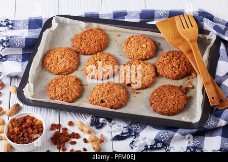 freshly baked Oatmeal Cookies with raisins and peanuts on a baking tray with wooden spatulas and kitchen towel, horizontal view from above, close-up - Stock Photo