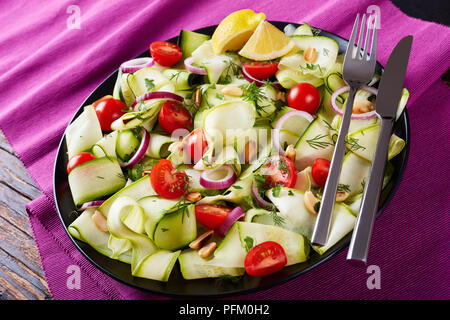 zucchini ribbon salad with tomatoes, roasted peanuts, red onion rings and greens served with fork and knife  on a black plate on an old wooden table,, - Stock Photo