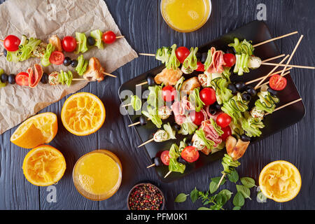 antipasto skewers with chicken meat, raw zucchini, cherry tomatoes,  mozzarella balls, salami slices, olives on a plate on a wooden table with orange  - Stock Photo