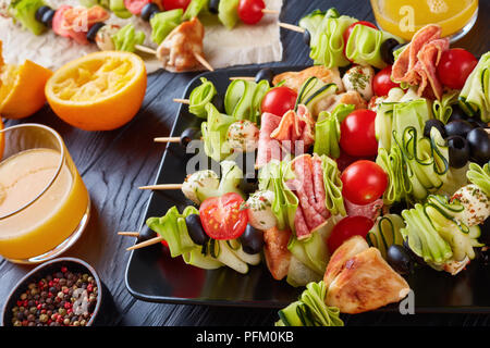 skewers with chicken meat, zucchini, tomatoes, mozzarella balls, salami slices, olives on a black plate on a wooden table with orange juice in glass c - Stock Photo