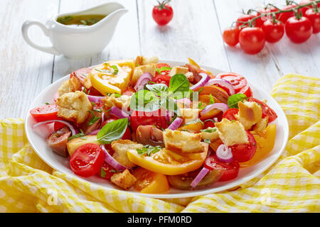 delicious fresh italian summer salad panzanella with tomatoes, croutons and onion rings on a white plate on a wooden table with sauce of olive oil at  - Stock Photo