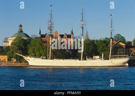 Sweden, Stockholm, af Chapman, built in 1888, the full-rigged former freighter and school ship has served as a popular youth hostel since 1949. Skeppsholmen Church, left and the Admiralty House, 1647-50, rebuilt 1844 to 1846, are in the background. - Stock Photo