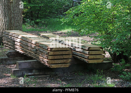 Two small stacks of sawn timber cut into planks and stacked off the ground on posts in a wood with a tree and shrubs in the background. - Stock Photo