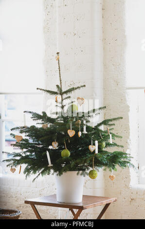 Small Christmas tree decorated with homespun Christmas decorations such as fabric balls, heart-shaped pastries and candles. - Stock Photo