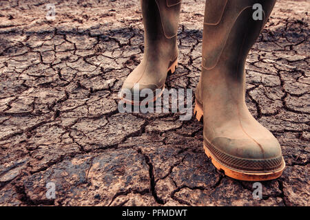 Farmer in rubber boots standing on dry soil ground, global warming and climate change is impacting crops growing and yield - Stock Photo