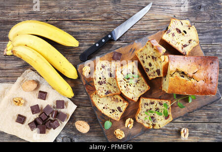 freshly baked delicious banana bread with walnuts and chocolate pieces cut in slices on cutting board. ingredients on rustic wooden table, view from a - Stock Photo