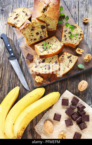 freshly baked delicious banana bread with walnuts and chocolate pieces cut in slices on cutting board. ingredients on rustic wooden table, vertical vi - Stock Photo