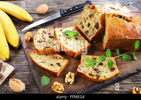 freshly baked delicious banana bread with walnuts and chocolate pieces cut in slices on cutting board. ingredients on rustic wooden table, american cu - Stock Photo