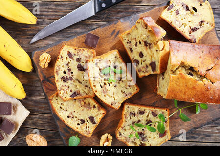 freshly baked delicious banana bread with walnuts and chocolate pieces cut in slices on cutting board. ingredients and knife on dark rustic wooden tab - Stock Photo