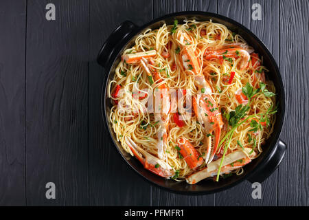 delicious spaghetti with Crab in Spicy White Wine Sauce in black dish on black wooden table, view from above - Stock Photo