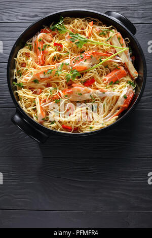 delicious spaghetti with Crab in Spicy White Wine Sauce, sprinkled with finely chopped parsley and Holland red chile in black dish on black wooden tab - Stock Photo