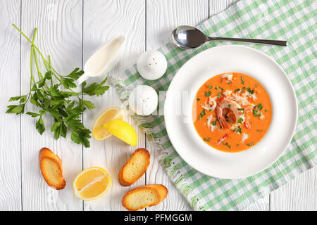 delicious hot bisque of shredded alaskan crab meat, shrimps and vegetables in a white wide rim soup bowl on wooden table with  spoon, toasted bread an - Stock Photo