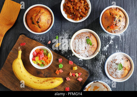 delicious freshly baked Homemade Banana Nut raisin Muffins in ceramic ramekins sprinkled with powdered sugar on black wooden table with ingredients at - Stock Photo