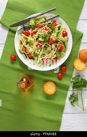 delicious fresh macaroni salad with cucumber slices, celery sticks, tomato and bean sprouts on white plate with toasted buns and sesame oil on wooden  - Stock Photo